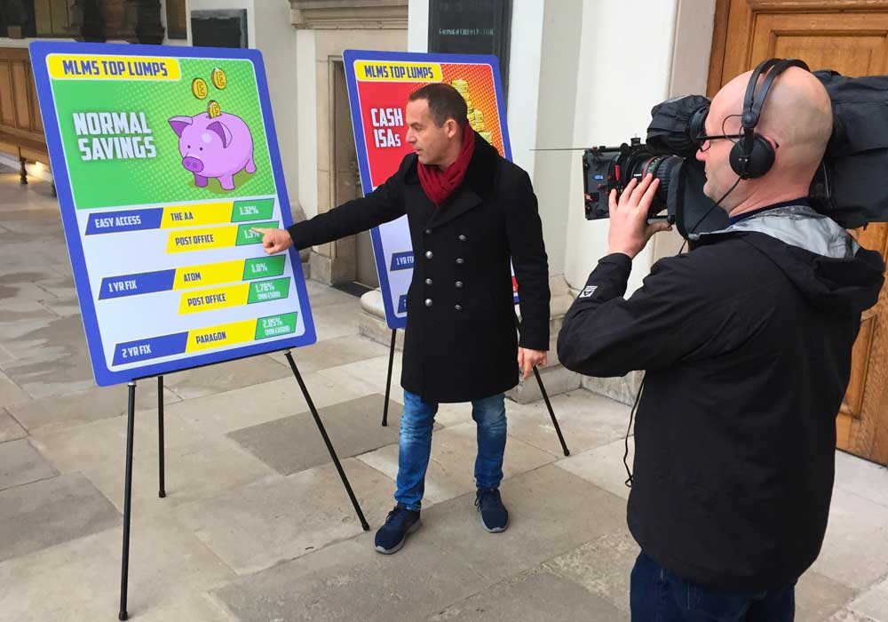 Martin Lewis being filmed talking about two MLMS Top Lumps Board with details about savings and Cash ISAs